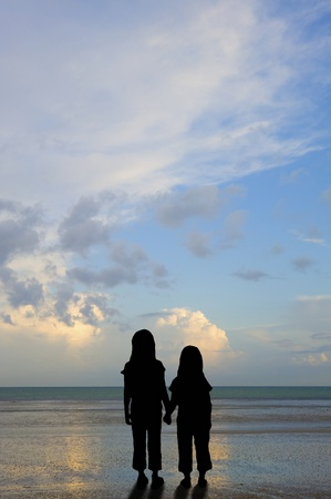 affected: Silhouette of abandoned or vulnerable children on sunset beach concept