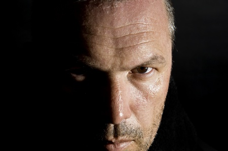 Dark and moody portrait of serious looking male adult photo