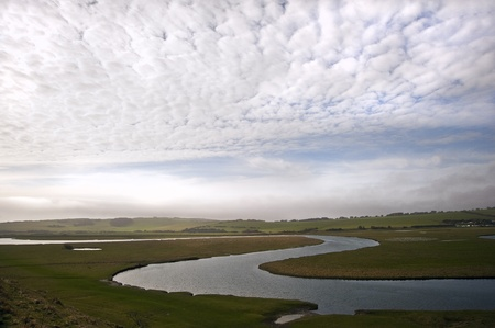 Meandering river twists through beautiful countryside landscape with cloudy blue sky overhead