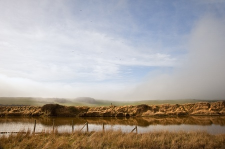 meandering: Meandering river twists through beautiful countryside landscape with cloudy blue sky overhead