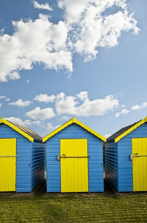 Bright colorful image of blue and yellow beahc huts against vibrant blue Summer sky photo