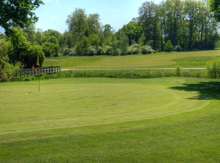 Beautiful vivid colorful image of golf course with green and fairway on sunny day photo