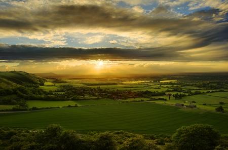 across: Beautiful landscape across countryside with sun beams lighting hills