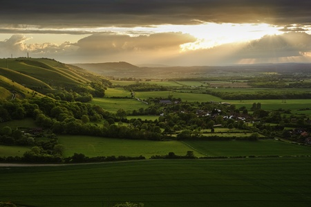 Beautiful landscape across countryside with sun beams lighting hills photo