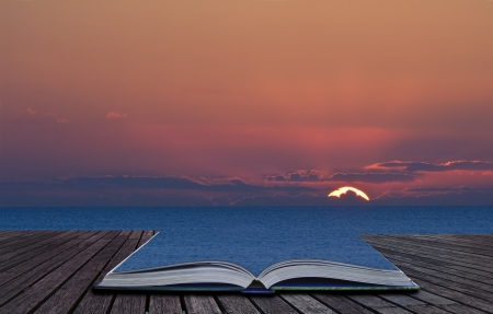 a wonderful world: Beautiful sunset contained in book spills out and blends into landscape background Stock Photo
