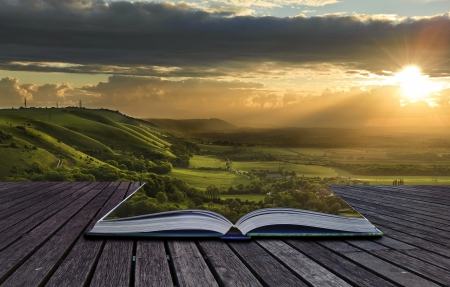 fantasy landscape: Beautiful sunset view across countryside spills out of magical book and creates stunning landscape background