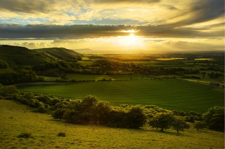countryside: Lovely landscape of countryside hills and valleys with setting sun lighting up side of hills whit sun beams through dramatic clouds