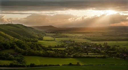 Lovely landscape of countryside hills and valleys with setting sun lighting up side of hills whit sun beams through dramatic clouds