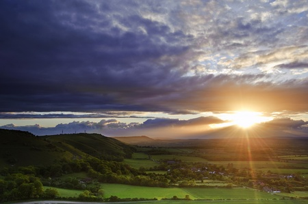 Lovely landscape of countryside hills and valleys with setting sun lighting up side of hills whit sun beams through dramatic clouds photo