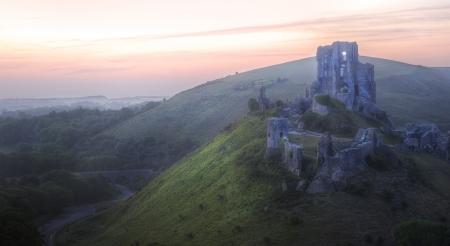 Beautiful dreamy fairytale castle ruins against romantic colorful sunrise photo