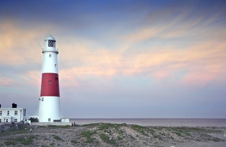 Old lighthouse is bathed in sunlight during beautiful sunset in Summer photo