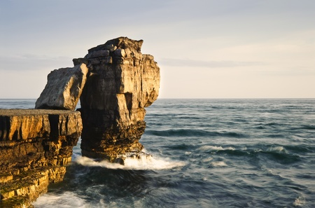 Waves crashing over rock formation cliffs at sunset with beautiful light on rock faces photo