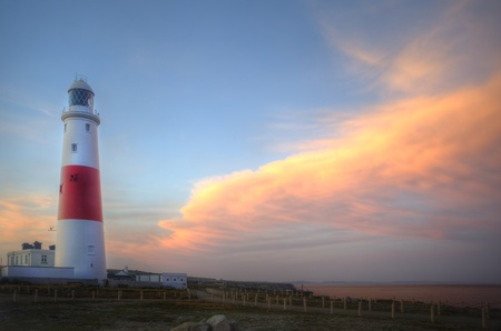 Old lighthouse is bathed in sunlight during beautiful sunset in Summer