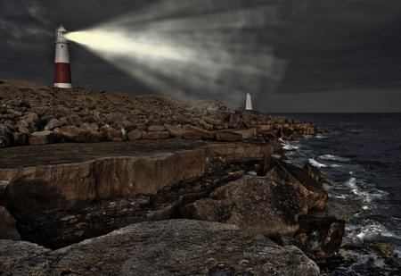 promontory: Old lighthouse with warning light on at night on promontory of rocks facing the ocean