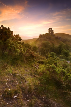Beautiful dreamy fairytale castle ruins against romantic colorful sunrise photo
