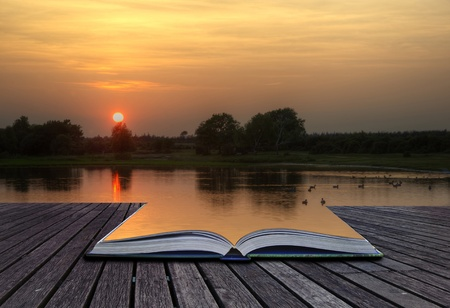 surreal landscape: Creative concept of beautiful simple image of sunset through tress reflected in lake in foreground coming out of magical book laid open Stock Photo