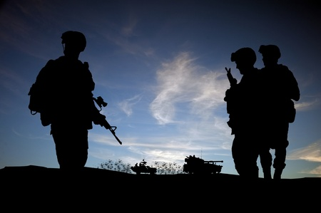 british man: Modern day soldiers in Middle East silhouette against sunset sky with vehicles in background Stock Photo