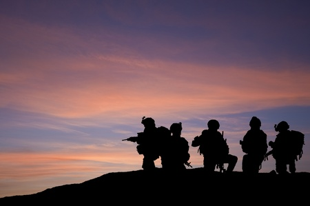 military invasion: Modern troops silhouette against sunset sky  in Middle East Stock Photo