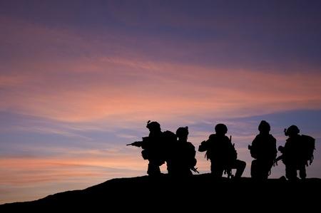 guerra: Silueta de tropas moderna contra el cielo del atardecer en Medio Oriente Foto de archivo