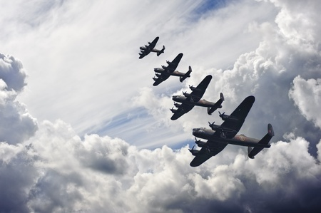 old world: Flight formation of Battle of Britain World War Two consisting of Lancaster bombers banking right Stock Photo