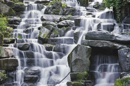 copse: Waterfall cascades flowing over flat rocks in forest landscape