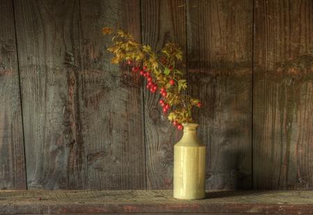 fiori secchi: Immagine di natura morta di fiori secchi in vaso rustico su sfondo di legno stagionato
