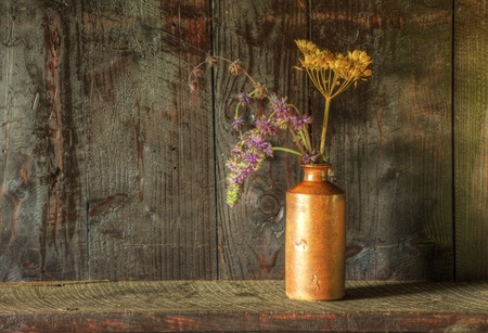 Still life image of dried flowers in rustic vase against weathered wooden background photo