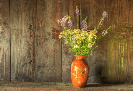 Still life image of dried flowers in rustic vase against weathered wooden background Stock Photo - 10671317