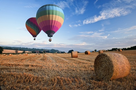 hot air balloons: Lovely sunset golden hour landscape of hay bales in field in English countryside