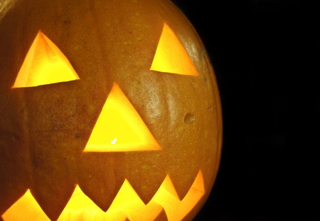 Scary Halloween pumpkin with carved face on black background photo