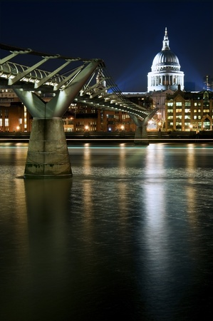 St Pauls Cathedral and Millennium Bridge in London at night with reflections in River Thames with vibrant colors and floodlights Stock Photo