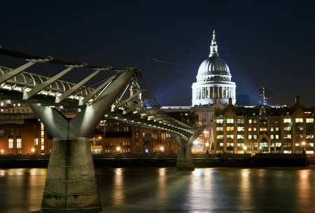 millennium bridge: St Pauls Cathedral and Millennium Bridge in London at night with reflections in River Thames with vibrant colors and floodlights Stock Photo