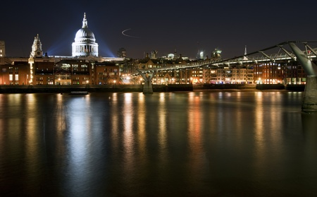 St Pauls Cathedral and Millennium Bridge in London at night with reflections in River Thames with vibrant colors and floodlights photo