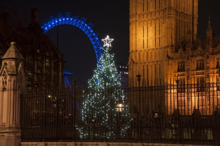 london city: Architectural detail of Houses of Parliament in London England with Christmas tree in foreground and London Eye in background Stock Photo