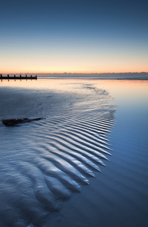 Beautiful low point of view along beach at low tide out to sea with vibrant sunrise sky photo