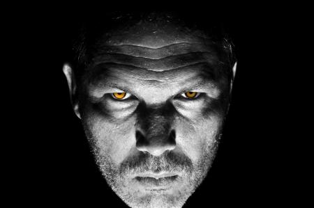 sudoroso: Retrato oscuro y de mal humor de los adultos seria masculina mirando con ojos brillantes de color naranja intimidaci�n