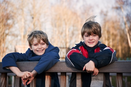 mischevious: Two young happy handsome brothers playing outdoors in Autumn Fall