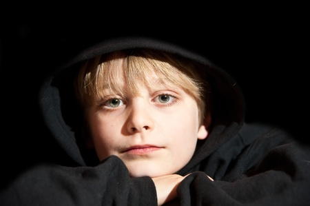 mischevious: Portrait of young handscome boy on black background wearing black hooded top Stock Photo