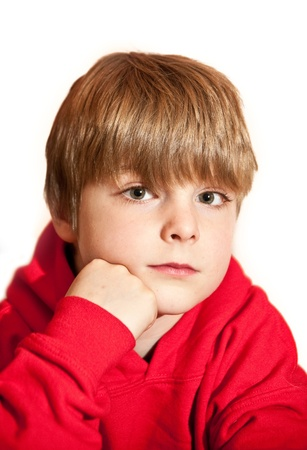 mischevious: Portrait of young handsome oy wearing red hooded top against white background