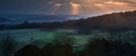 godlike: Lovely Winter landscape over countryside of sun beams lighting the hills