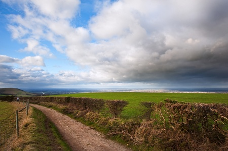 Stunning moody sky with beautiful cloud formations and colors over countryside landscape of path leading into distance photo