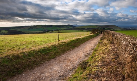 Stunning moody sky with beautiful cloud formations and colors over countryside landscape of path leading into distance Stock Photo - 12324116