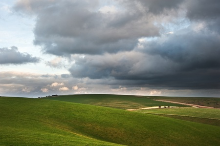 hill: Stunning cloud formations during stormy sky over countryside landscape with vibrant colors Stock Photo