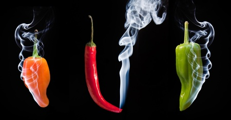 Smoke comes out of tips of hot chilli peppers in orange red and green photo