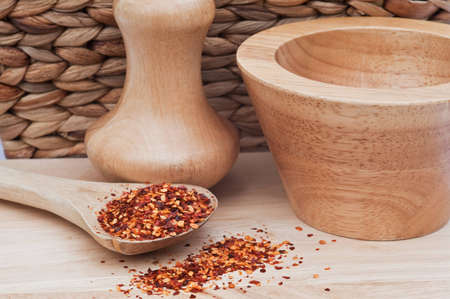 Crushed chillies on wooden spoon in rustic kitchen setting photo
