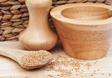 serv: Mustad seeds in rustic kitchen setting with wooden pestle and mortar, wooden serv ing spoon and selective focus
