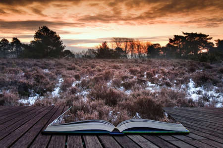 Beautiful Winter sunrise landscape over vibrant snow covered countryside landscape comming out of pages in magic book photo
