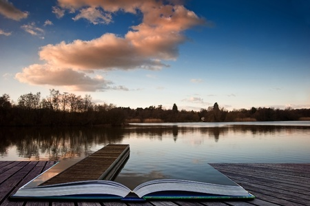 long lake: Lovely image of late sunset sky over calm lake landscape with long fishing jetty pier and vibrant colors coming out of pages in magical book