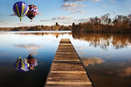 Mooi beeld van hete lucht ballonnen over zonsondergang landschap van houten pier vissen op kalm meer met heldere reflecties