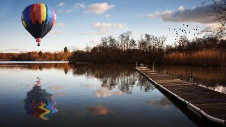 Mooi beeld van hete lucht ballon over de late zonsondergang hemel over kalme landschap met lange vissen steiger pier en levendige kleuren